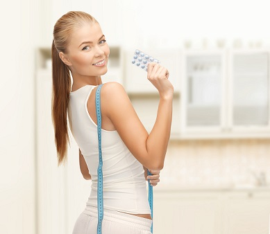 smiling woman with measuring tape and diet pills