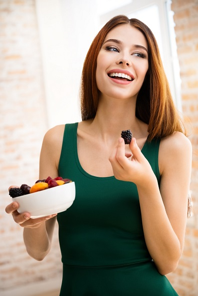 Young happy smiling woman with plate of fruits, indoors. Beauty and dieting concept. Weight lossing, by healthy eating.