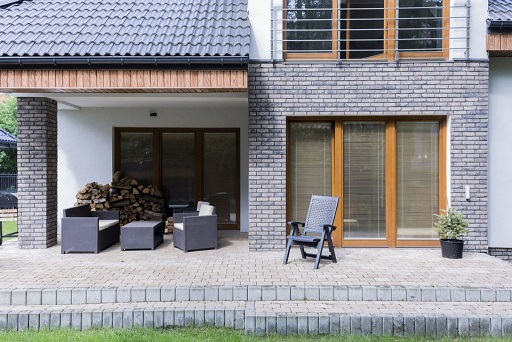 Cobbled terrace behind the modern house, with a set of dark garden furniture