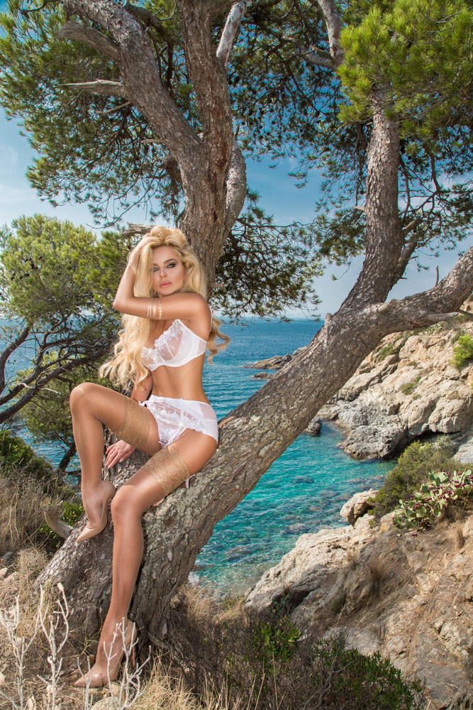 Beautiful young very sexy blond hair female model amazing girl lies on an old tree with an amazing view of the rough sea and rocks in fleshy nude erotic lingerie with long shapely legs in high heels