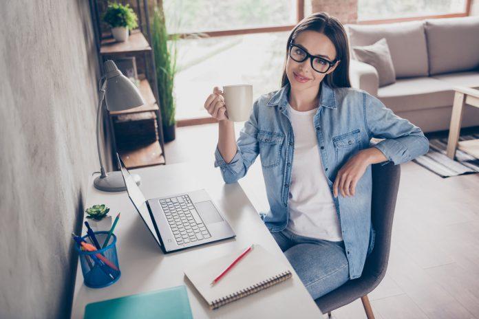 Młoda kobieta w okularach pije herbatę podczas pracy przy komputerze w swoim domowym biurze